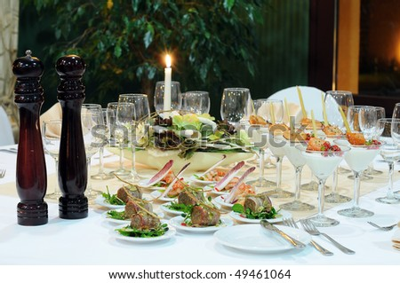 Luxury table setting for a banquet in restaurant. Table with the candle, wineglasses, snacks and cocktails.
