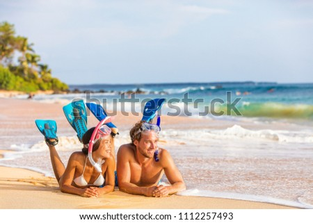 Luxury travel leisure activity watersport fun people relaxing after snorkel swim. Beach couple on summer snorkeling holiday sport activity. Young adults enjoying vacation lying down on sand.