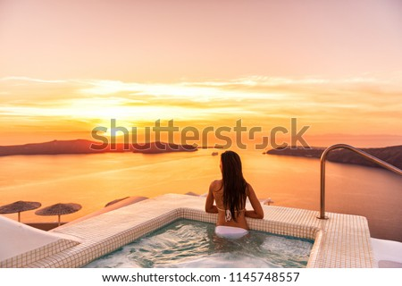 Luxury travel Santorini vacation woman swimming in hotel jacuzzi pool watching sunset. Europe resort destination holiday for honeymoon getaway. #1145748557