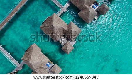 Luxury travel vacation aerial of overwater bungalows resort in coral reef lagoon ocean by beach. View from above at sunset of paradise getaway Moorea, French Polynesia, Tahiti, South Pacific Ocean. #1240559845