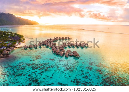 Photo of Luxury travel vacation aerial of overwater bungalows resort in coral reef lagoon ocean by beach. View from above at sunset of paradise getaway Moorea, French Polynesia, Tahiti, South Pacific Ocean.