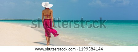 Luxury travel vacation elegant lady walking on beach in pink fashion skirt wrap relaxing on Caribbean holidays during winter. Panoramic banner landscape crop for background.