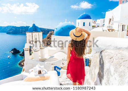Luxury travel vacation Europe holiday Santorini girl in hat and red fashion dress walking 3 blue domes famous tourist attraction. Summer sun holidays adventure.