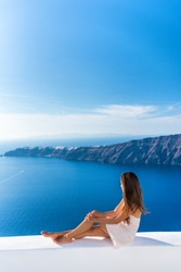 Luxury travel vacation Europe tourist woman relaxing at fancy hotel resort balcony in greek Santorini island, Greece with view over the Mediterranean Sea and Oia. Elegant girl living jetset lifestyle.