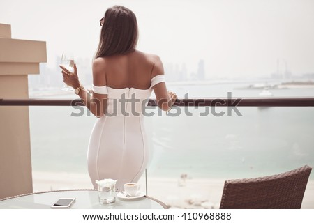 Luxury travel vacation woman with champagne glass looking at view on Dubai famous travel destination. Elegant young lady wearing sexy dress on holidays. Travel concept. (soft focus)