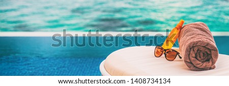Luxury vacation banner background of sunscreen, sunglasses for sun protection on towel and lounger at hotel infinity swimming pool for sun tan summer relaxation panoramic banner. Foto d'archivio ©
