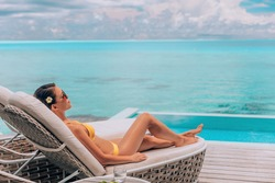 Luxury vacation in paradise Bora Bora high end resort hotel bikini woman relaxing lying on lounger sunbathing by the swimming pool at overwater villa suite.