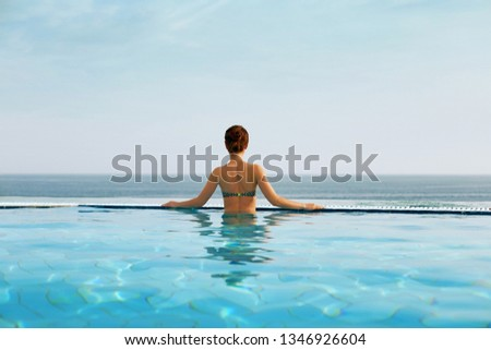 Luxury vacation travel woman relaxing in infinity swimming pool on summer beach resort.  Spa relaxation watching  in nature landscape background. #1346926604