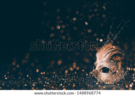 Luxury venetian mask on dark godlen bokeh background. New year and christmas party celebration design banner. Carnival masquerade fantasy costume ball. Stock photo ©