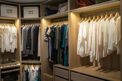 Luxury walk in closet / dressing room with lighting and jewel display. Dresses, handbags, blouses and sweaters on hangers in the wardrobes. Hoizontal.