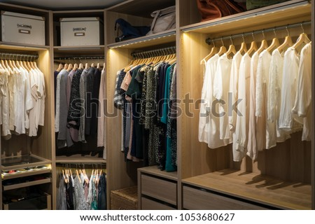 Luxury walk in closet / dressing room with lighting and jewel display. Dresses, handbags, blouses and sweaters on hangers in the wardrobes. Hoizontal. #1053680627