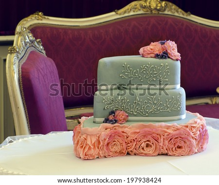 Luxury wedding cake decorated with pink roses on table; antique furniture in background.