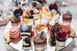 luxury wedding catering, table with modern desserts, cupcakes, sweets with fruits. delicious candy bar at expensive wedding reception. space for text. shower. holiday celebration