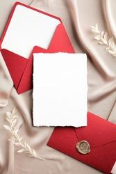 Luxury wedding invitation card mockup and envelopes on beige silk. Flat lay, top view, copy space. Elegant wedding stationery set.