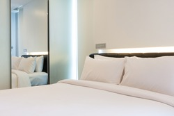 luxury white bedroom with reflexion view in mirror.