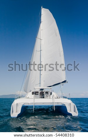 Luxury white catamaran boat in the ocean with blue sky