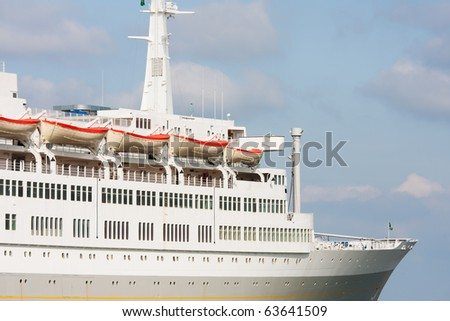 Luxury white cruise ship shot at angle at water level on a clear day with blue sky.