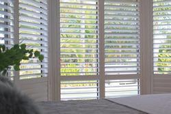 Luxury white indoor plantation shutters in bedroom - selective focus