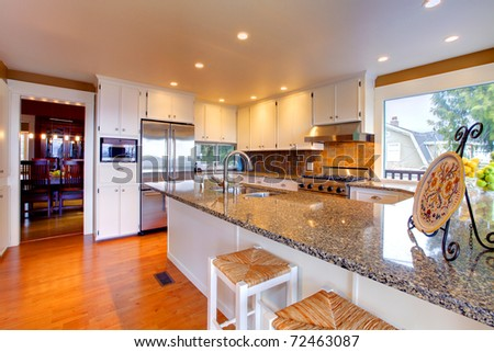 Luxury White Kitchen, Oak Floors And Beautiful Granite Stock Photo