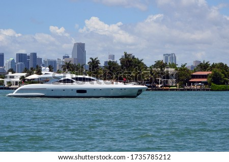 Photo of  Luxury white motor yacht idling off luxury Miami Beach island homes on the Florida Intra-Coastal Waterway with Miami tall building skyline in the background.