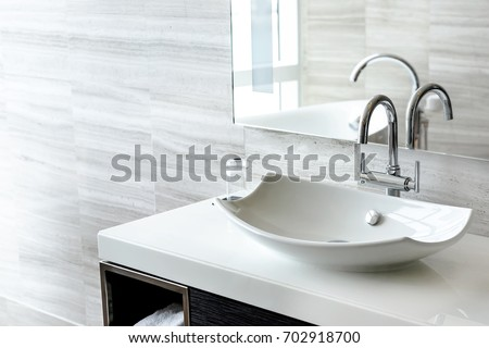 Luxury white porcelain sink on a bathroom table - Shutterstock ID 702918700