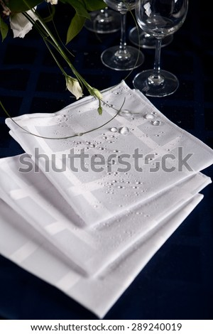 Luxury white serviettes on the blue table-cloth #289240019
