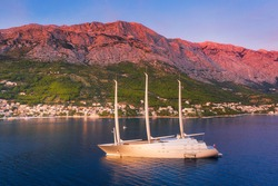 Luxury yacht and blue sea at sunset in summer. Aerial view of big modern sail boat. Top view of beautiful futuristic yacht, water, city, green trees, mountains, purple sky. Travel in Adriatic sea