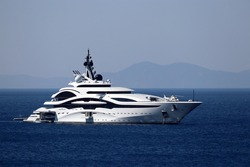 Luxury yacht with helipad and helicopter sailing in a sea, side view. White futuristic boat on mountain island background