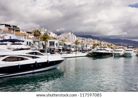 Luxury yachts and apartment houses in Puerto Banus on Costa del Sol, near Marbella in southern Spain, Andalusia, Malaga province. - stock photo