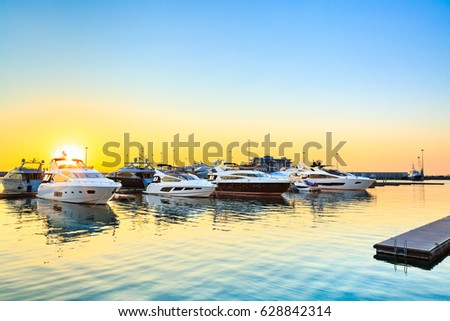 Luxury yachts docked in sea port at sunset. Marine parking of modern motor boats and blue water. Relaxation and fashionable vacation.