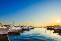 Luxury yachts, sailing and motor boats docked in sea port at sunset. Marine parking of modern motorboats, blue water. Travel and fashionable vacation.
