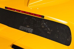 Luxury yellow roadster fragment. Rear ventilation grate and stop lights. Italian car design