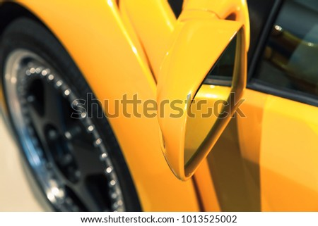 Luxury yellow sports car mirror, close up photo. Italian car design