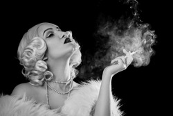 luxury young woman smoking on black background, monochrome