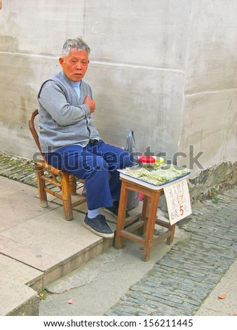 LUZHI, SHANGHAI, CHINA -Â?Â? OCTOBER 30: man selling peanuts at a street corner. The ancient village is a Shanghai tourist attraction with 100000 visitors per year. October 30, 2004 Luzhi, China.