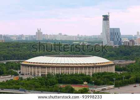Luzhniki Stadium stands among green trees at dull day, panorama of Moscow