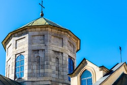 LVIV, UKRAINE - April, 2021: The Dome with christian cross on the tower of Ancient Armenian church of the Assumption of Mary in Lviv, Ukraine