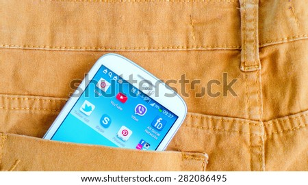 LVIV, UKRAINE - May 03, 2015: White Samsung Smart Phone with   social media applications  on screenin the pocket of orange jeans #282086495