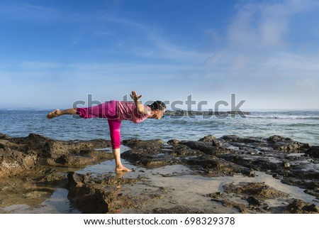 Ly Son Island, Quang Ngai Province, Vietnam - July 30, 2017: A woman on the volcanic cliff is practicing yoga in the dawn light on Ly Son Island, Quang Ngai Province, Vietnam #698329378