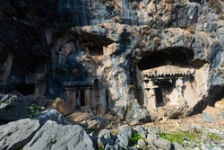 Lycian rock hewn tombs carved into mountainside in ancient Pinara city, Mugla Province, Turkey