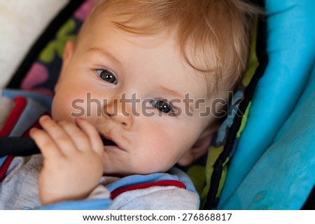 lying baby, smiling baby, baby has something in mouth, hold with teeth, lying in deck chair for baby #276868817