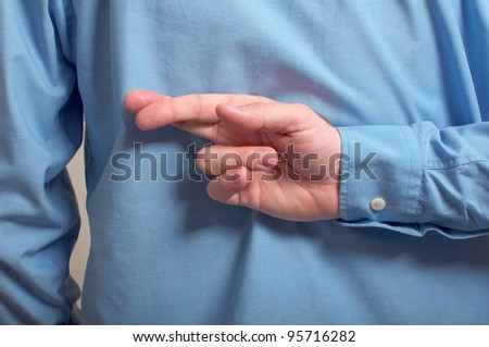 Lying businessman. Businessman in black shirt crossing his fingers behind his back