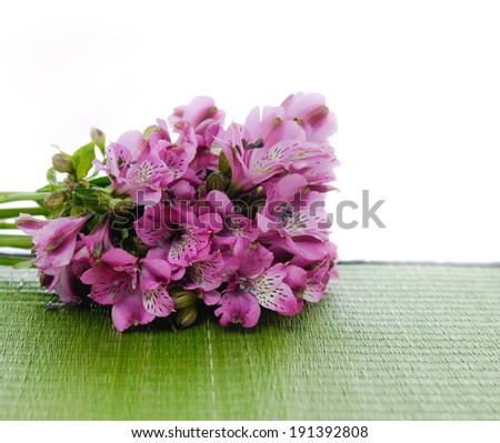 Lying down bouquet of orchid and wet Stones on green straw mat