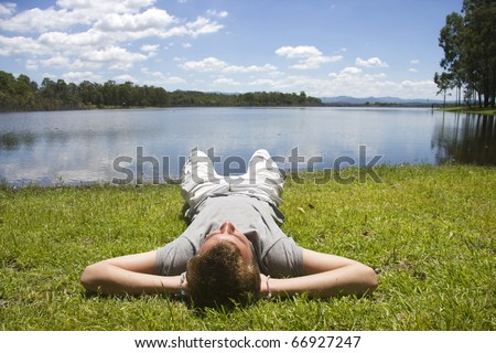 Lying Down On His Back With His Hands Behind His Neck A Young Mans Unwinds To The Sounds Of Nature