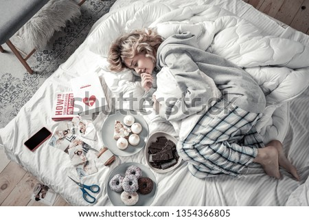 Lying in bed. Emotional woman wearing pajamas lying in bed near books and food after breakup #1354366805