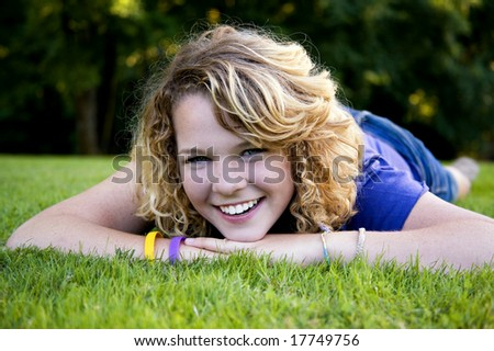 Lying in the grass and having a laugh is this cute high school graduate