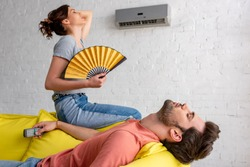 lying man with closed eyes and woman with hand fan suffering from heat at home