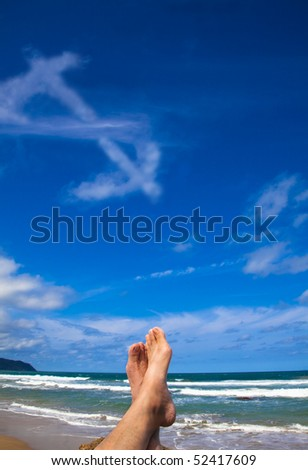 Lying on the beach with dollar symbol cloud - stock photo