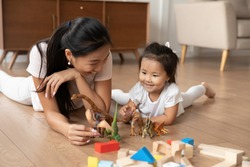 Lying on warm wooden floor asian mom play game with little daughter holds dinosaurs toys heap of colorful construction blocks nearby. Spend time have fun together educational activity with kid concept