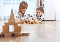Lying on warm wooden floor mom play game with little son holds construction blocks. . Underfloor heating. Underfloor heating and comfort house concept.